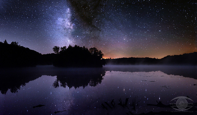 Four-panel panorama of the Milky Way over a misty lake